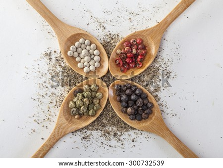 Pepper mill on a white isolated background with peppers green, red, black and white pepper next to the wooden spoon
