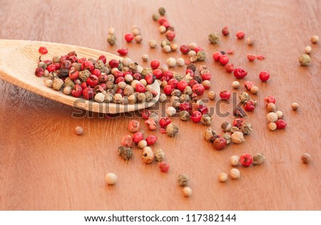 Pepper mix in a spoon on wooden table