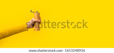 pepper shaker in hand over yellow background, panoramic mock-up with space for text