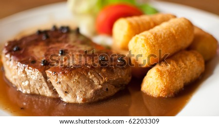 pepper steak with salad, pepper sauce and potato croquettes