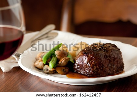Pepper steak with vegetables and a glass of red wine