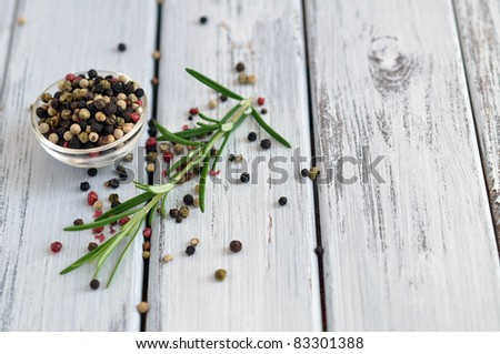 Peppercorn mix in a glass bowl and fresh rosemary on an old white table
