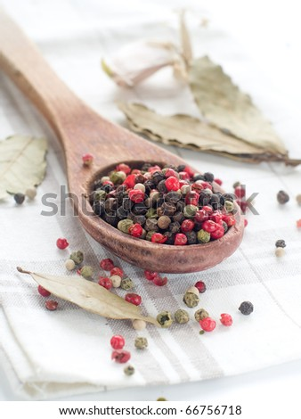 Peppercorns in wooden spoon with garlic on background
