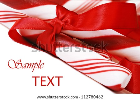 Peppermint candy sticks with red satin ribbon on white background with copy space.  Macro with shallow dof.