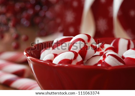Peppermint candy sugar twists in dark red dish with holiday decor, gifts, and candy canes in soft focus in background.  Macro with extremely shallow dof.