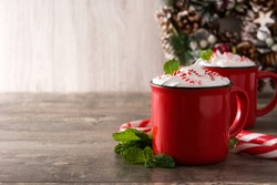 Peppermint coffee mocha decorated with candy canes for Christmas on wooden table Copy space