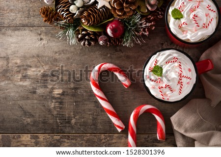 Peppermint coffee mocha decorated with candy canes for Christmas on wooden table. Top view. Copy space #1528301396