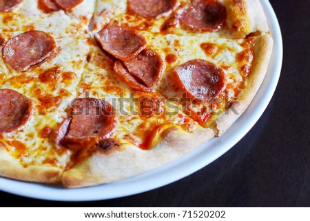 Pepperoni pizza on white dish , served hot , closeup view , original from italian restaurant