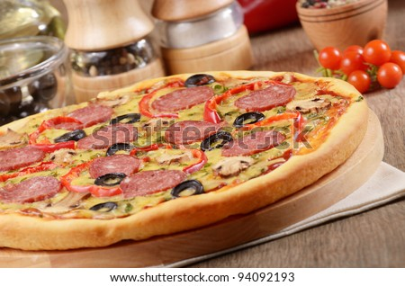 Pepperoni pizza with mushrooms and paprika on the kitchen table with spices