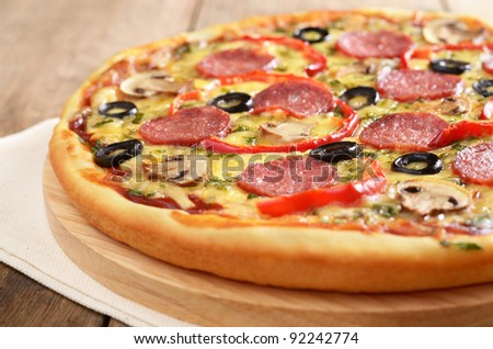 Pepperoni pizza with mushrooms on the wooden board closeup