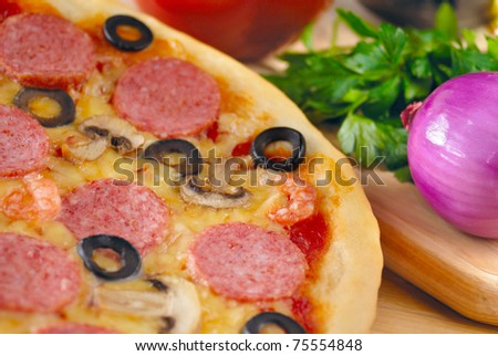 Pepperoni pizza with mushrooms, peppers and olives on the kitchen table