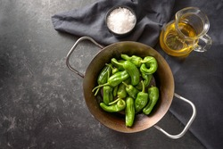 Peppers de padron or fresh green pimientos in an iron pan with olive oil and sea salt, ingredients for  Spanish tapa or appetizer, dark gray slate background, copy space, high angle view from above