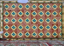 Peranakan tile mosaic as typically found on traditional Chinese shop houses, with turquoise blue flowers on a scalloped red and maroon background and geometric floor tiles in the foreground.
