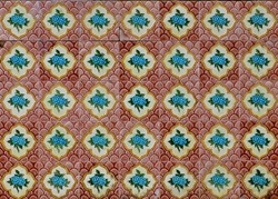 Peranakan tile mosaic as typically found on traditional Chinese shop houses, with turquoise blue flowers on a scalloped red and maroon background.
