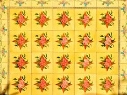 Peranakan tile mosaic of red flowers on a yellow background, typical facade found on traditional Chinese shop houses in China town, throughout South East Asia.