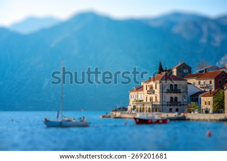 Perast city in Kotor bay on the sunset with beautiful mountains and boat floating in Montenegro - stock photo