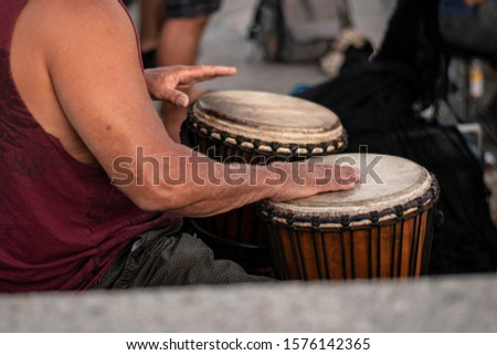 Percussionist up close and drumming on djembe drums.