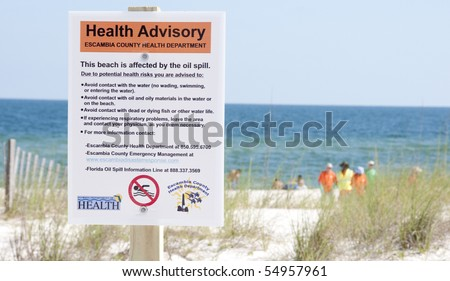 PERDIDO KEY, FL - JUNE 10:  A warning sign is posted at the beach as the oil washes ashore on June 10, 2010 in Perdido Key, FL.  Oil spill workers can be seen in the distance.