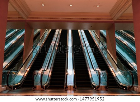 Perfect and balanced escalators with mirrors on the sides and light soft reflections on the floor, ceiling, and metal.