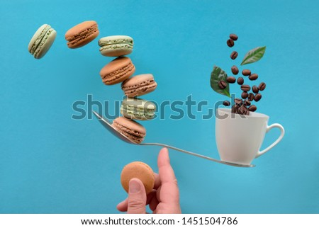 Perfect balance concept composition. Balancing cup of coffee and macaronos on a finger, flat lay on blue mint color paper