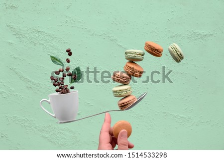 Perfect balance concept composition. Balancing cup of coffee and macaronos on a finger in front of a wall painted in green mint color