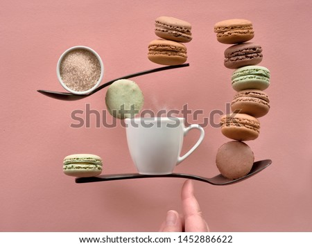 Perfect balance concept still life on coral color paper backgound. Balancing cup of coffee, sugar and macarons on a finger.