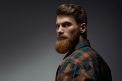 Perfect beard. Close-up of young bearded man standing against grey background
