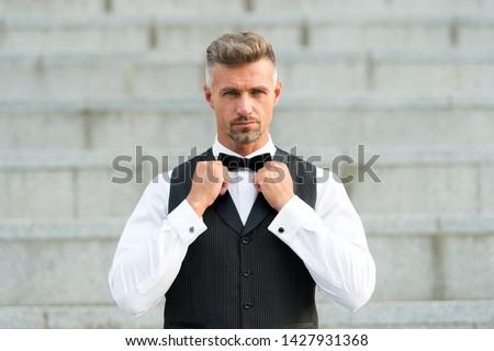Perfect bow tie. Gentleman modern style. Guy well groomed handsome bearded gentleman macho wear shirt and vest. Barber shop for groom. Confidence in his glance. Restaurant waiter. Elegant gentleman.