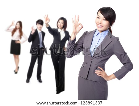 Perfect - business woman making the ok sign with her team behind. Young pretty Asian businesswoman isolated on white background.