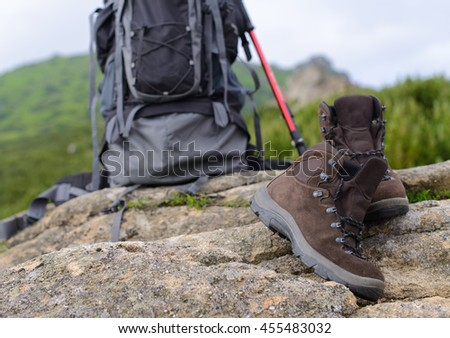 Perfect camping. Close up of boots and rucksack backpack in mountains. Camping explorer equipment footwear concept #455483032