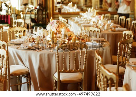 Perfect classy chairs stand at rich dinner tables served with golden candleholders and vases