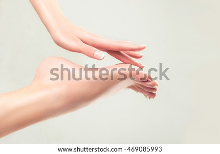Perfect clean female feet . Beautiful and elegant groomed girl\'s hand touches her feet . Spa ,scrub and foot care .