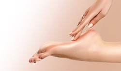 Perfect clean female foot . Beautiful and elegant groomed girl's hand touches her feet . Spa ,scrub and leg care .