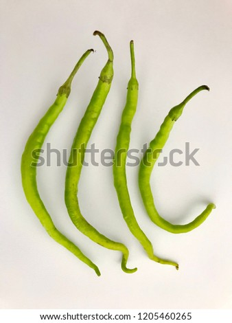 Perfect composition of 4 pieces of green pointed peppers that stands on a white background.