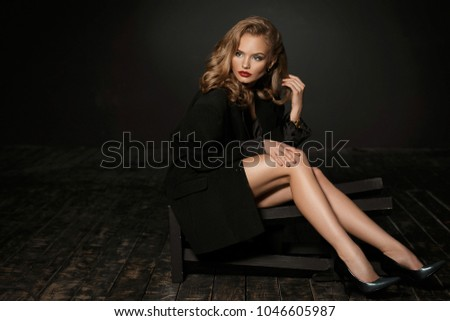 Perfect fashion studio shot of seductive beautiful girl without liberie in one black jacket sitting on high black chair against black background.