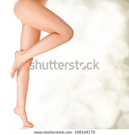 Perfect female legs on golden blurred background