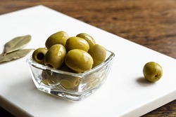 perfect green olives in a glass bowl close up on white stone board