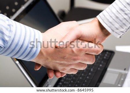 Perfect handshake of business people on the background of laptop