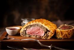 Perfect homemade juicy Beef Wellington, tenderloin dish on rustic wooden table
