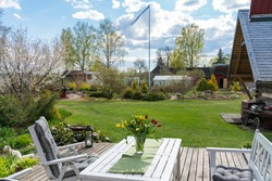 Perfect looking garden. Amazing sunny weather. Nice sitting area on terrace, flowers on the table, couple of chairs. Flag waving on the back. Lawn freshly cut. Garden of the year Estonia