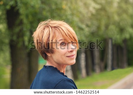 Perfect Mature beauty. Beautiful redhead older woman with trendy layered bob haircut in park