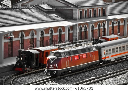 Perfect models of the older (steam) and newer (diesel) locomotives and passenger trains wait on the railway station.