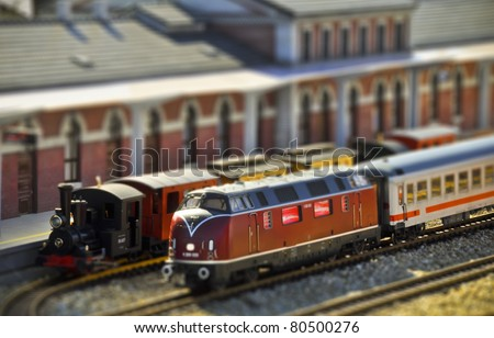 Perfect models of the older steam and newer diesel locomotives and passenger trains wait on the railway station. Tilt-shift technique.