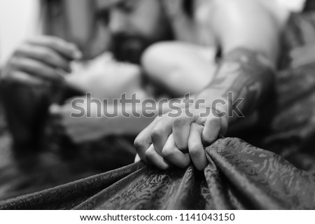 Perfect morning and sex concept. Couple in love holding hands tight, close up. Man with beard and tattoos holds female hand, selective focus. Male and female hands crossed on red patterned sheets