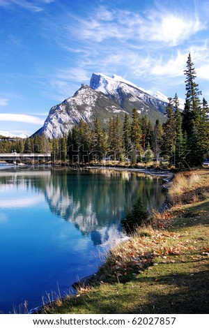 Perfect mountain scene with reflection and trees photographed in Banff, in the Canadian Rockies.