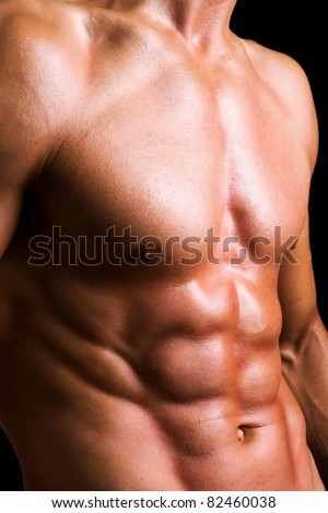 Perfect naked male torso against black background