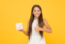 Perfect package. Thank you. Child happy face holds big gift box yellow background. Kid girl delighted gift. Girl hairstyle adorable happy face celebrate birthday. Kid happy love birthday gift.