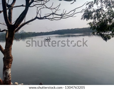 Perfect Picture of lake, where the shun is about to set and fisher is in his boat for fishing. Pic was take from the bank of pond with the angel of a tree which has no leaf.