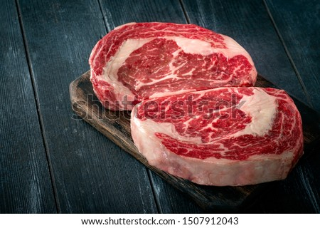 Perfect raw rib eye beef steak on black wooden background, close-up