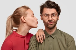 Perfect relationships concept. Beautiful blonde woman kisses her boyfriend in cheek, leans at shoulder, wears red blouse, isolated over white background. Puzzled man doesnt want to kiss with lover